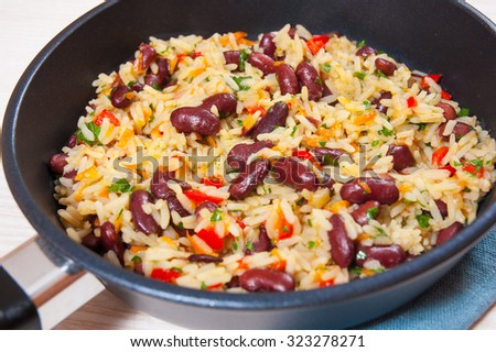 rice with red beans and vegetables in a frying pan - stock photo