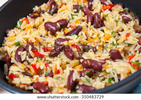 rice with red beans and vegetables in a frying pan