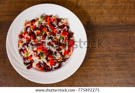 rice with red beans and vegetables on wooden table. with copy space. top view.