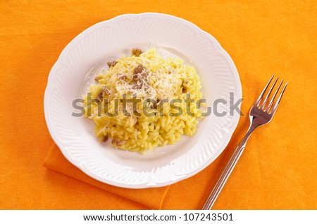 Rice with saffron and sausage in white dish - stock photo