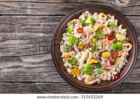 rice with seafood and broccoli in a clay bowl on the old wooden table, view from above - stock photo
