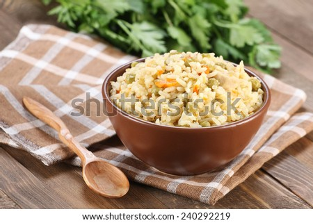 rice with vegetables in a ceramic bowl on a wooden boards background - stock photo