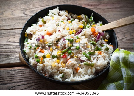 Rice with vegetables in a pan. Rustic Style.
