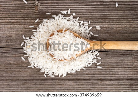 rice with wooden kitchen spoon on wooden table - stock photo