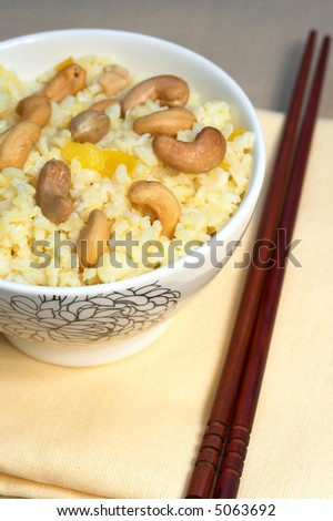 Rice Yellow Peppers and cooked cashews with chopsticks