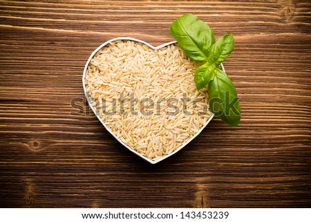 Ricel, heart-shaped box. Wooden surface. - stock photo