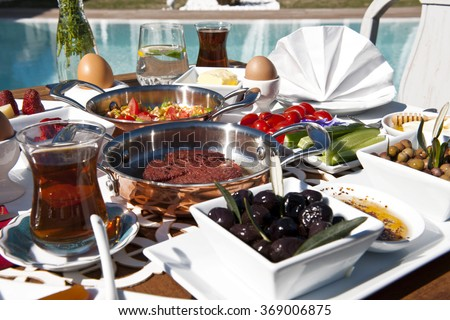Rich and delicious Turkish breakfast on a big table near the swimming pool - stock photo