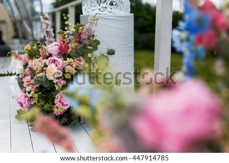 Rich bouquet made of pink flowers stand behind a white box on the porch - stock photo