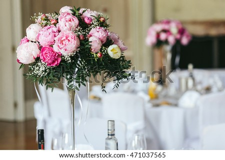 Rich bouquet of pink peonies stands on the dinner table