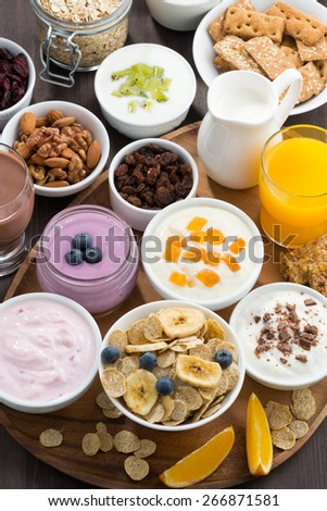 rich breakfast buffet with cereals, yoghurt and fruit on wooden tray, vertical, top view, close-up - stock photo