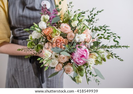 Rich bunch of pink peonies and white eustoma roses flowers, green leaf in glass vase. Fresh spring bouquet. Summer Background.  - stock photo