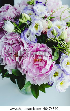 Rich bunch of pink peonies peony and lilac eustoma roses flowers in glass vase on white background. Rustic style, still life.  - stock photo
