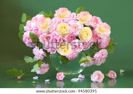 Rich bunch of tea and cream roses on green background