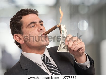 Rich businessman lighting cigar with $100 dollar bill
