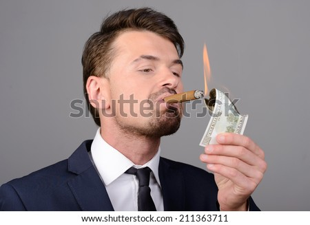 Rich businessman lighting cigar with $100 dollar bill - stock photo