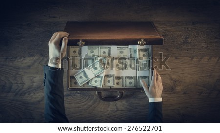 Rich businessman opening a leather briefcase filled with dollar packs, top view, unrecognizable person - stock photo