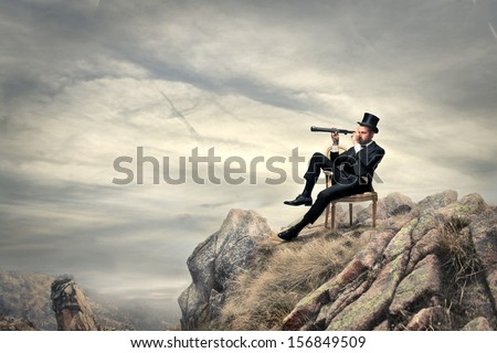 rich businessman sitting on a chair in the mountain looking the landscape with spyglass - stock photo