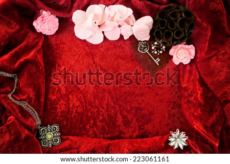Rich color, very soft crushed velvet fabric as background and frame with floral potpourri, vintage jewelry and old fashioned skeleton key.  - stock photo