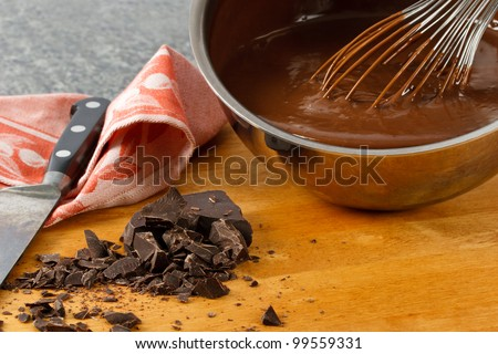 Rich, creamy chocolate pudding in a sauce pan with chocolate chunks and kitchen utensils