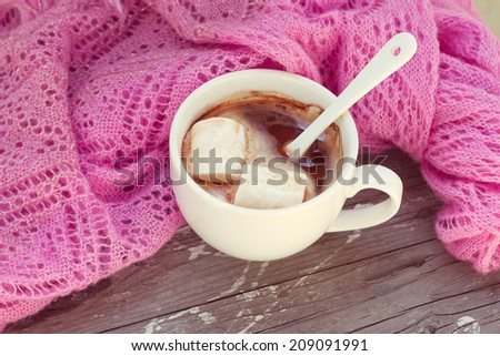 rich cup of hot chocolate wrapped in a cozy winter scarf - stock photo