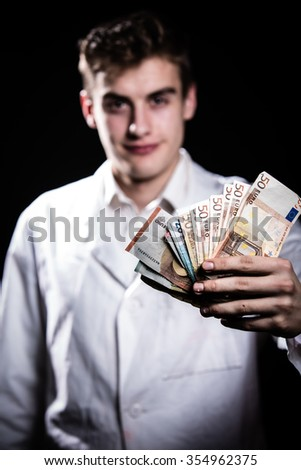 Rich doctor.Young male doctor holding money.Corruption and criminal in Health Care Industry.Satisfied young male doctor after recieving bribe isolated on background - stock photo