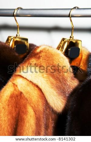 Rich female fur coats on sale in shop - stock photo
