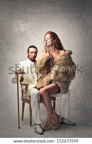 rich gangster in white dress sitting on an armchair and beautiful woman with fur smokes cigarette - stock photo
