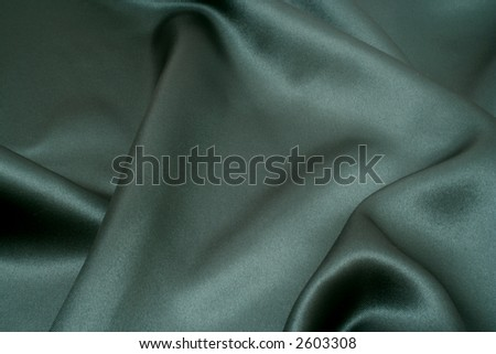 Rich green satin fabric background, diffused slightly to give a softer appearance - stock photo
