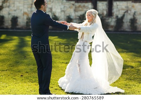 rich groom and bride holding hands outdoor background wall grass warm and sunny