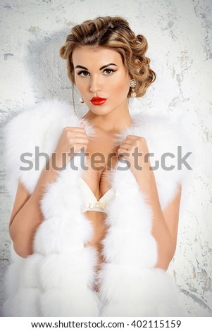 Rich lifestyle. Beautiful sexual woman wearing jewelery and white fur vest. Beauty, fashion. Evening make-up and hairstyle. - stock photo