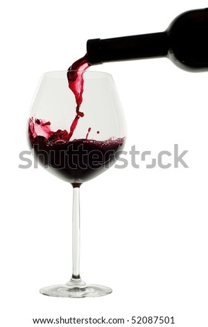 Rich red wine being poured into balloon wineglass. Isolated on white background. - stock photo