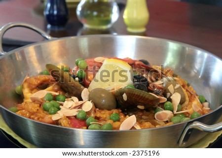 Rich seafood paella with baked almond slices and whole olives