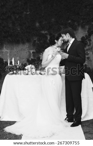 rich stylish happy bride and groom kissing  holding goblets with champagne  near a white wedding table decorated with flowers peonies and candles Rome Italy black and white - stock photo