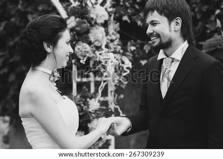 rich stylish happy bride and groom smiling holding hand near a white wedding arch decorated with flowers peonies Rome Italy black and white