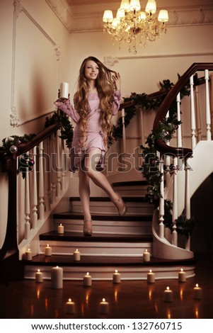 Rich woman on staircase with a candle - stock photo