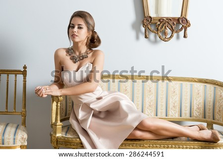 Rich woman with aristocratic style lying on antique sofa in aristocratic room and looking in camera. Wearing elegant pink dress and precious necklace.