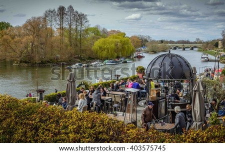 RICHMOND UPON THAMES, UK - APR 10: People enjoy the sunny weather in Richmond Upon Thames near London on April 10, 2016. The town is in proximity of a large number of parks, including Richmond Park - stock photo