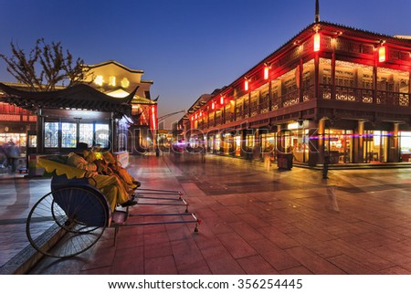rickshaws waiting for customers tourists in pedestrian area of ancient Nanjing city in China after sunset on a busy illuminated street - stock photo