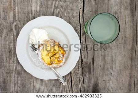 Ricotta cheese and pine nut cake served with cream and a glass of lemonade on a pine table top