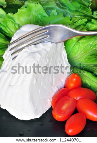 Ricotta with cherry tomatoes and lettuce, sliced with a fork