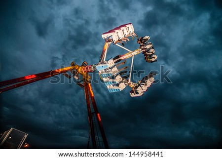 Ride at county or state fair in evening - stock photo
