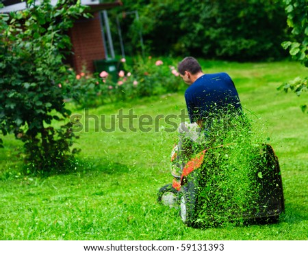 Ride-on lawn mower cutting grass. Focus on grasses in the air - stock photo