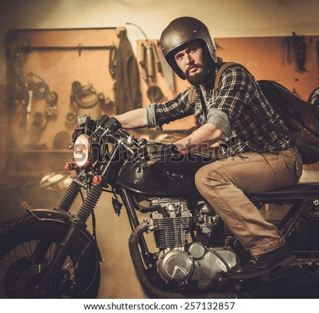 Rider And His Vintage Style Cafe Racer Motorcycle In Customs Garage