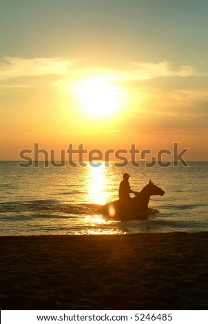 Rider in the sea on the sunset - stock photo