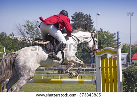 Rider jumping on horseback competing in equestrian tournament - stock photo