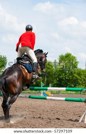 Rider jumping over the barrier at the event - stock photo