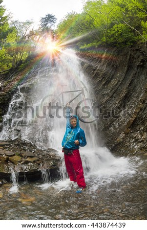 rider on a mountain bike is bathed in a mountain waterfall Guk under the mountain Hamster and Synyak wild alpine forest during Ukrainian Carpathian travels on trails Ukraine, Vorokhta - stock photo