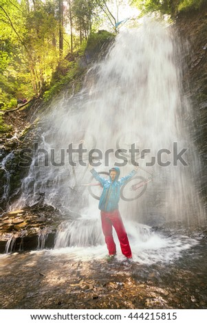 rider on a mountain bike is bathed in a mountain waterfall Guk under the mountain Hamster and Synyak wild alpine forest during Ukrainian Carpathian pteshestviya on trails off-road in the Carpathians - stock photo
