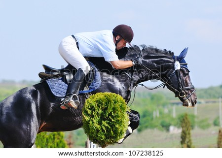 Rider on black horse over a jump - stock photo