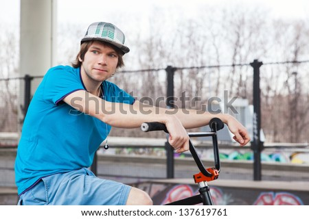Rider posing with bicycle near ramp - stock photo